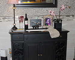 This painted black vanity sits on bun feet, and features two scolled, push to open doors on either side. The wainscott makes it really stand out.